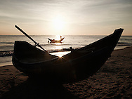 Ray of light shines on a fishing boat resting on shore, Dong Hoi, Quang Binh Province, Vietnam, Southeast Asia. A man sets sail in the background.