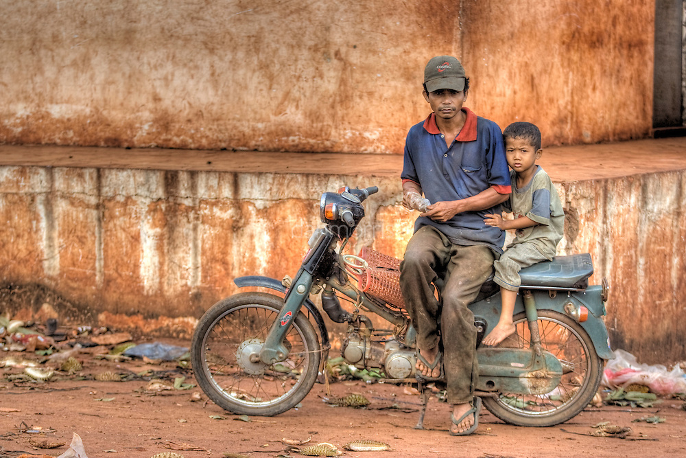 Father and son sit on scooter in Snuol, Cambodia