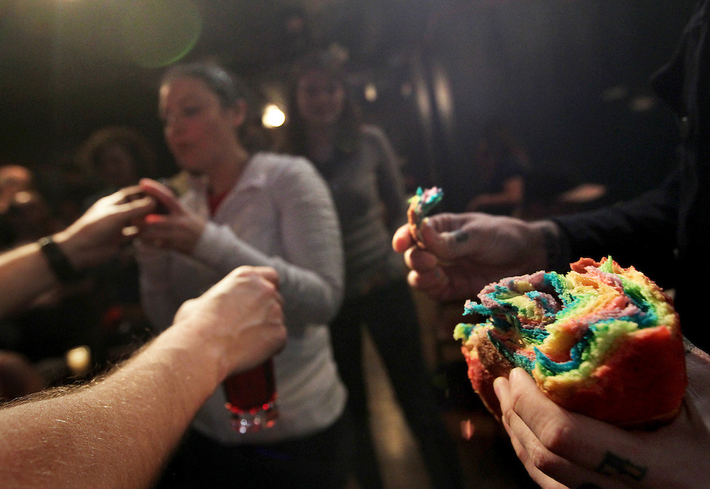 Revolution Church pastor Jay Bakker (hands at right) serves rainbow bread Communion while friend Tony Jones (hands at left) serves wine during a gathering at Bryant Lake Bowl, a Minneapolis bar, the day before Minnesota passed legislation to become the 12th state in the US to legalize gay marriage.