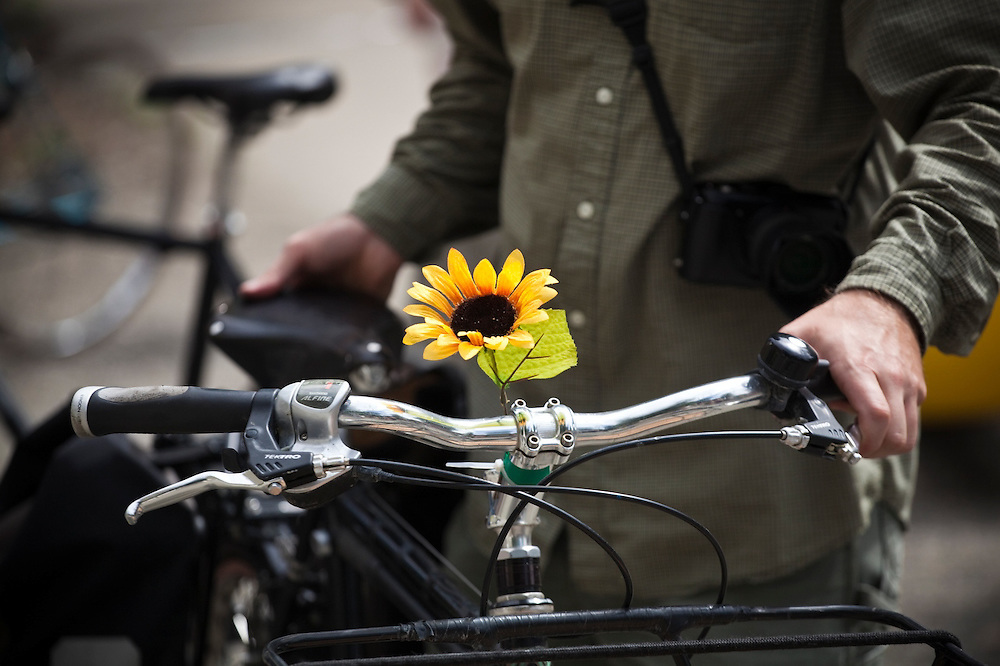 A plastic flower on a bicycle among a group of activists preparing to ride bicycles from downtown Boulder, Colorado to the nearby coal-fired Valmont Power Plant to protest its continued operation. The protesters planted sunflowers and erected signs on vacant land outside the entrance to the plant.