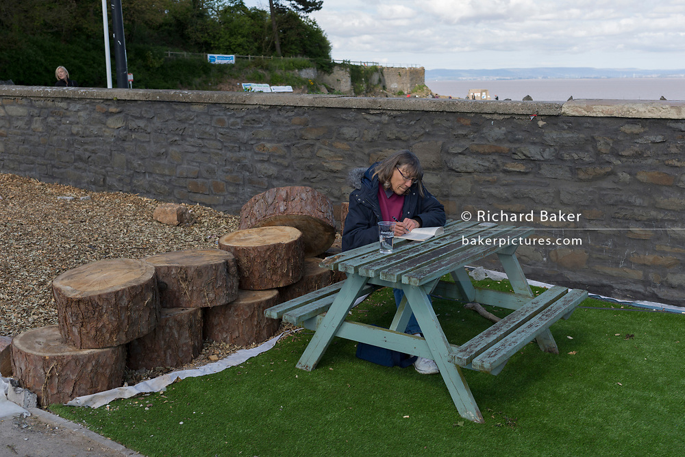 A lady reads on a bench at Clevedon on 22nd April 2017, in North Somerset, England.