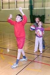Children playing a game of basket ball in the sports hall of their local leisure centre,