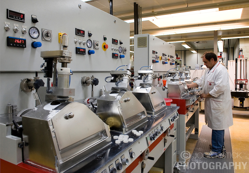 SOLMS, GERMANY - MAY-18-2009 - A technician monitors a row of polishing machines at yet another stage in the lens production process. (Photo © Jock Fistick)