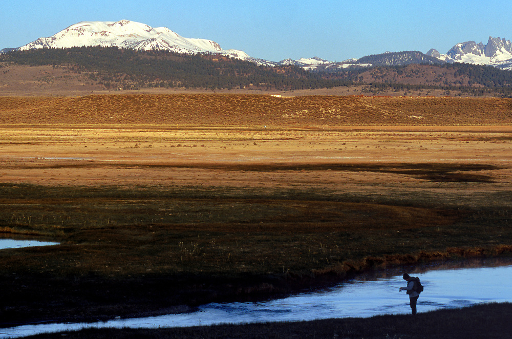 A fisherman finds peace along a section of the Upper Owens River with Mammoth Mountain as a backdrop as the sun rises over the Eastern Sierras.