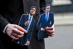 © licensed to London News Pictures. London, UK 18/03/2015. A TV presenter holding cardboards of Ed Miliband and David Cameron in Downing Street on the Budget Day, Wednesday, 18 March 2015. Photo credit: Tolga Akmen/LNP