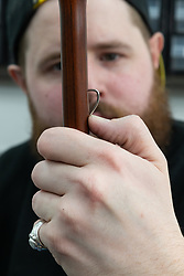 Umbrella maker Lee checks the fit of a spring in the shaft of an umbrella. Craftspeople at Fox Umbrellas Ltd, a company in Croydon, Surrey, that has been going for over 150 years hand build quality umbrellas. Croydon, Surrey, March 06 2019.