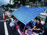 24 OCTOBER 2017 - BANGKOK, THAILAND: People waiting to enter the royal cremation site huddle under a tarp they're using a rain shelter during a monsoon rain. People started camping out along Atsadang Road in Bangkok near the royal cremation site on Monday. The gates won't open until Wednesday morning and the cremation isn't until Thursday night, so most people will sleep outside, on sidewalks and footpaths for three nights. Hundreds of thousands of people are expected to try to get into Sanam Luang, the site of the cremation of Bhumibol Adulyadej, the Late King of Thailand, but the site will only hold about 60,000 people. The Thai government has built replica crematoriums around Bangkok to accommodate the overflow crowds.        PHOTO BY JACK KURTZ