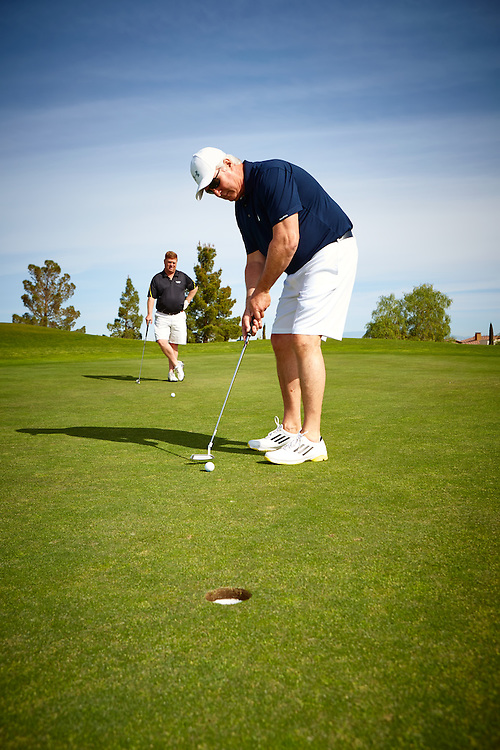 Chuck Swink putts with Bill Copeland looking on , AT&T fun day at Rio Secco Golf Club .