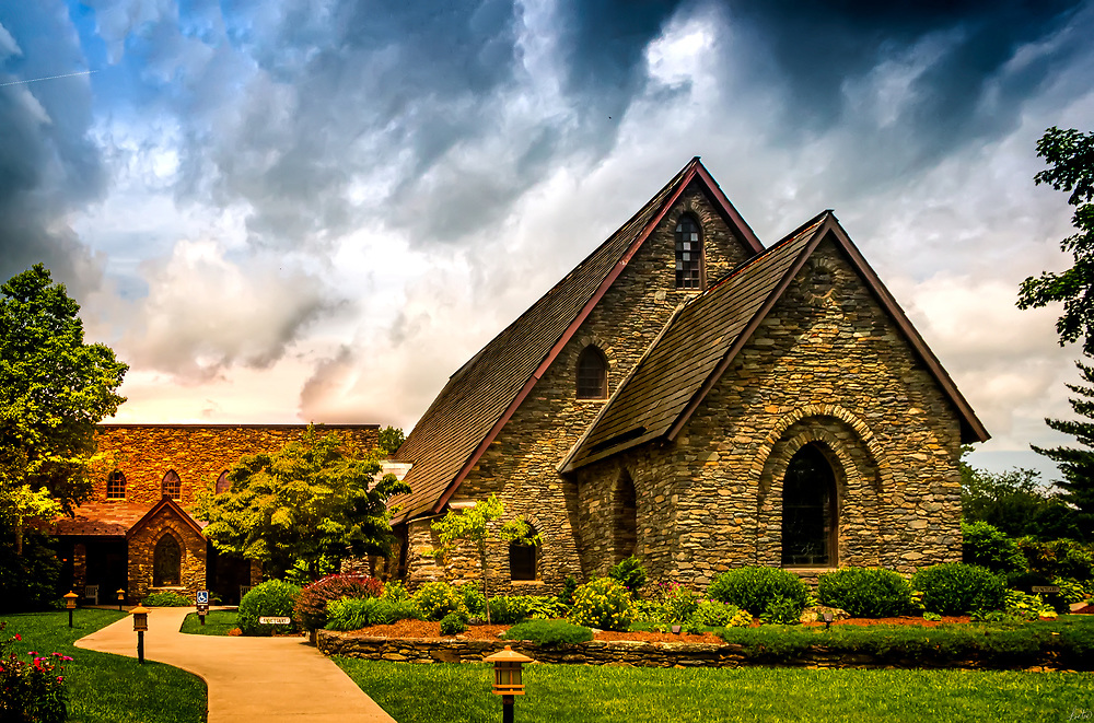 Rumple Memorial Church on a partly cloudy day with the sun breaking through and lighting the church