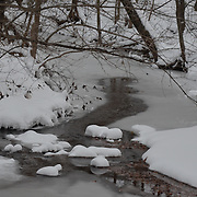 A partially frozen stream with snow covered banks
