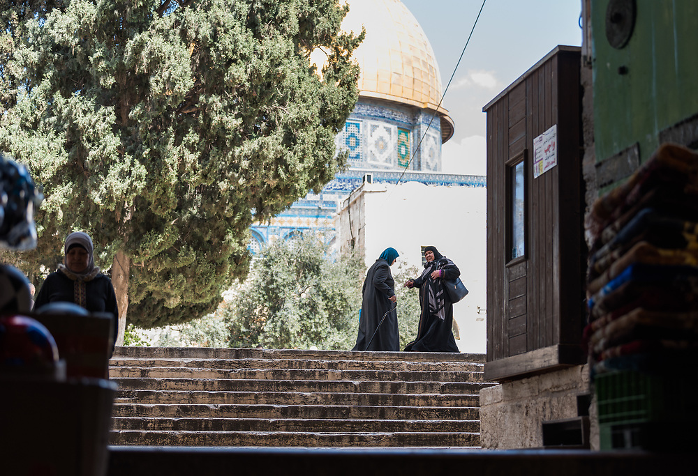 19 April 2019, Jerusalem: Two women greet as they pass by one another by the entry point to Al Aqsa mosque from the Suq al Qattanin (the Cotton Market) in Jerusalem.