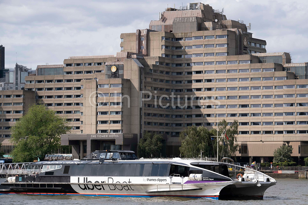 Typhoon Clipper which runs part of the Uber Boat taxi service on the Thames river, passes The Tower Hotel near Tower Bridge, on 11th June 2021, in London, England. Thames Clippers operates a fleet of 20 boats on the River Thames, with departures from 23 piers across London from Putney to Woolwich.