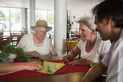 Senior women and nursing staff playing ludo board game at rest home, Bavaria, Germany, Europe
