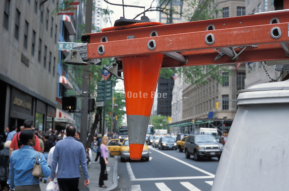 Ladder on top of a van with an upside down orange cone