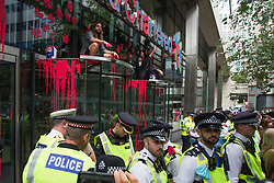 © Licensed to London News Pictures.  27/08/2021. London, UK. Members of Extinction Rebellion  stained Standard Chartered Bank with artificial blood as demonstration marching through central London. They protesting against the use of Fossil fuels. Photo credit: Marcin Nowak/LNP