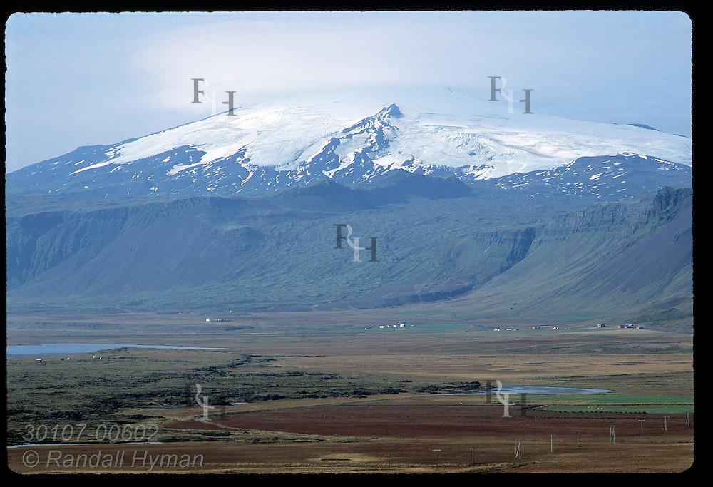 Snaefellsjokull glacier, its twin peaks shrouded in clouds, towers over coastal farms of Snaefellsnes peninsula; Iceland.