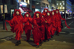 London, UK. 9 October, 2019. Climate activists from the Extinction Rebellion Red Brigade walk along the Strand on the evening of the third day of International Rebellion protests to demand a government declaration of a climate and ecological emergency, a commitment to halting biodiversity loss and net zero carbon emissions by 2025 and for the government to create and be led by the decisions of a Citizens' Assembly on climate and ecological justice.
