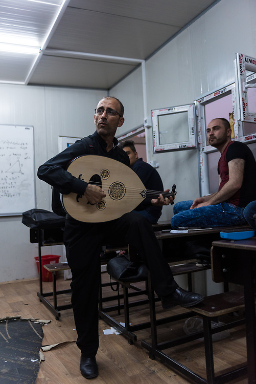 Father Duraid Barber plays the oud during an oud lesson at Mart Shmoni church, a Syriac Catholic church in Ankawa, a suburb of Erbil, Iraq. Most of the parisioners are IDPs, pushed out of their homes in Qaraqosh during the 2014 ISIS advance. Father Duraid, age 47, is from Qaraqosh and has been a priest for 16 years.  (May 15, 2017)