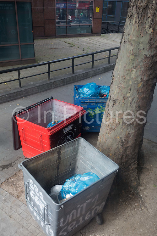 Waste bins beneath an urban tree at Elephant & Castle in the south London borough of Southwark, on 5th August 2019, in London, England.
