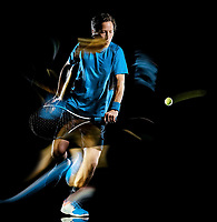 one caucasian tennis player man isolated black background in light painting speed motion