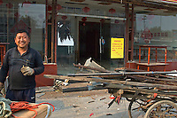 China, Beijing, Chaoyang, San Jian Fang, 2008. Part of a large group of itinerant recyclers, this man specializes in anything made of metal. An empty Chaoyang Street restaurant is behind him.