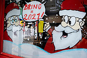 As the UK government tells the nation to prepare for the worst two weeks of the Coronavirus pandemic, a warning aimed at the population to stay at home and minimise contact with others, but in the week when new vaccination centres are opening, a Christmas-themed window of a pub remains closed two weeks after the holiday, on 11th January 2021, in the City of London, England.