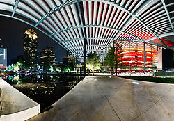 Shade canopy and reflecting pool of Winspear Opera House framing buildings of downtown, Dallas, Texas, USA.  Designed by Pritzker Prize winning architect Norman Foster.