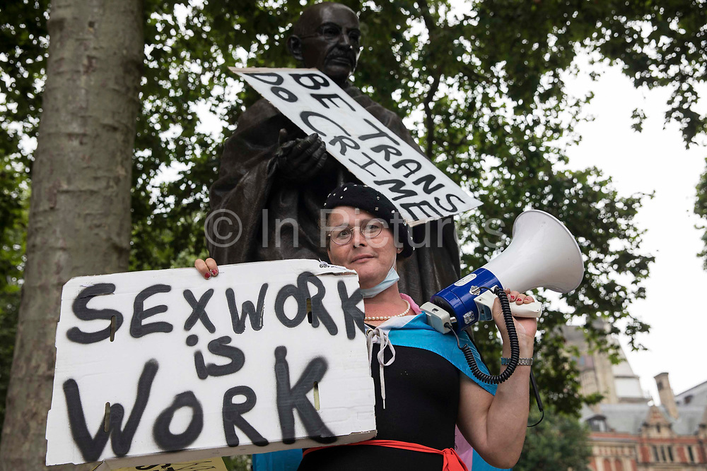 A trans rights campaigner poses with a sign in front of the statue of Gandhi in Parliament Square before the first-ever Reclaim Pride march on 24th July 2021 in London, United Kingdom. Reclaim Pride replaced the traditional Pride in London march, which many feel has become too commercial and strayed from its roots in protest, and was billed as a People's Pride march for LGBTI+ liberation. Campaigners called for the banning of LGBTI+ conversion therapy, the reform of the Gender Recognition Act, the provision of a safe haven for LGBTI+ refugees and for LGBTI+ people to be decriminalised worldwide and marched in solidarity with Black Lives Matter.