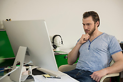 Mid adult man working on computer in living room, Munich, Bavaria, Germany