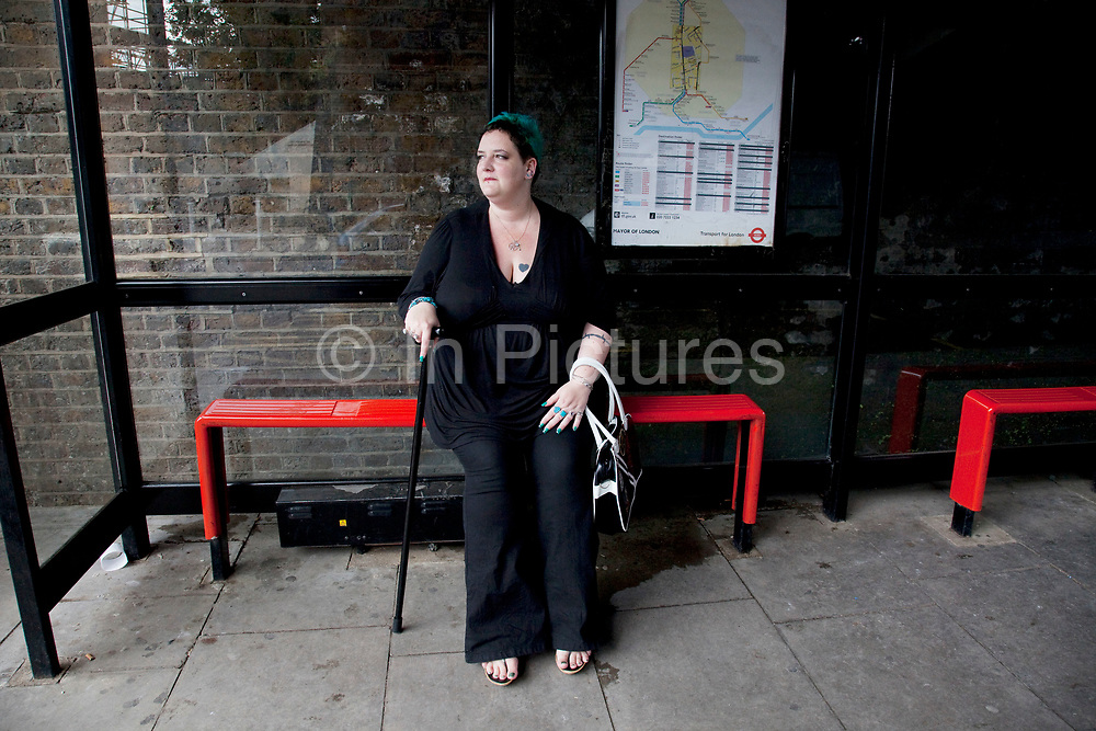 Mother Louise Irwin-Ryan waiting for a bus at the bus stop in her neighbourhood of Barnsbury, near to Kings Cross, North London. Louise is on various benefits to help support her family income, and housing, although recent government changes to benefits may affect her family drastically, possibly meaning they may have to move out of London. Louise Ryan was born on the Wirral peninsula in 1970.  She moved to London with her family in 1980.  Having lived in both Manchester and Ireland, she now lives permanently in North London with her husband and two children. Through the years Louise has battled to recover from a serious motorcycle accident in 1992 and has recently been diagnosed with Bipolar Affective Disorder. (Photo by Mike Kemp/For The Washington Post)