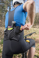 Rear view of mountain biker removing out muesli bar from pocket