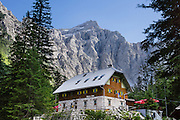 """At the end of the road in Vrata Valley, Slovenia, admire the close mountain grandeur of Triglav, Dolkova Spica, Skrlatica, and Stenar from Aljazev Dom hut [a dormitory refuge at 1015m elevation which serves meals, has 8 rooms with 23 beds, 115 communal beds; Tel: +386 (0)4 589 51 00 or +386 (0)4 589 10 30]. Walk easily 0.5 km to wide views at the """"Monument to fallen Partisans,"""" and higher trails lead to steeper, technical routes. Mount Triglav (9396 feet) is the highest peak in the Julian Alps, which were named Julius Caesar, who founded some nearby cities. The scenic Vrata valley extends from Mojstrana village through a mixed forest of beech, spruce and fir, along crystal clear Triglavska Bistrica creek, to the north face of Triglav, in Triglavski narodni park, Slovenia's only national park. In 1991, Slovenia declared full sovereignty from Yugoslavia, in Europe. 80% of its 2 million people speak Slovene. In 2004, Slovenia joined NATO and the EU (European Union), and later adopted the Euro € currency. Slovenia is the richest Slavic nation per capita."""