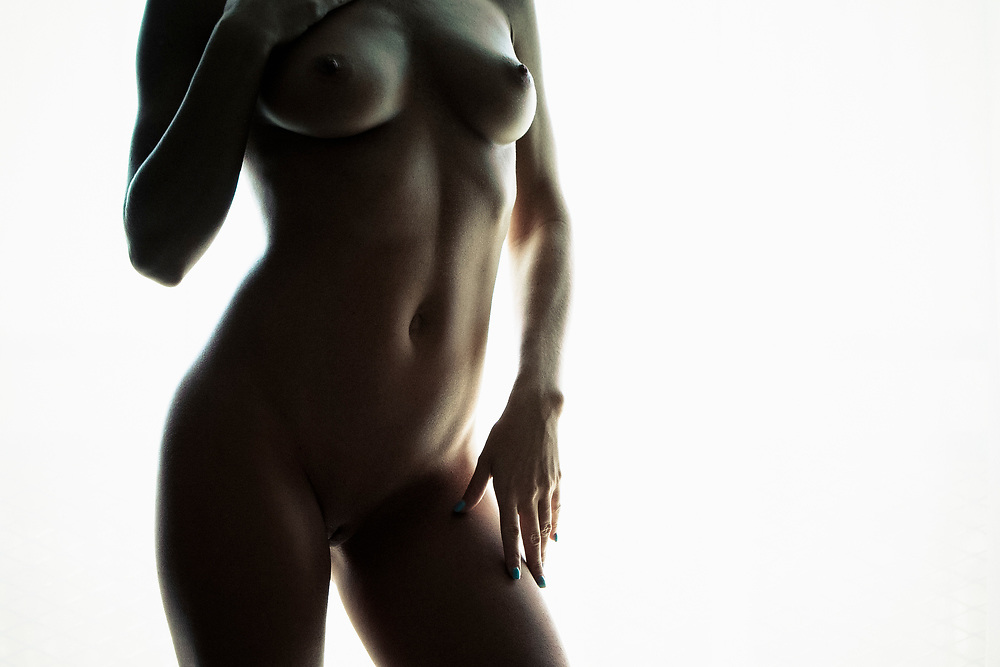 Side lit photo of woman's nude torso standing in front of window with drapes