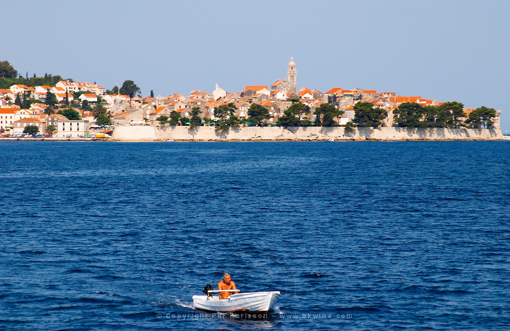 View across the sea on the town of Korcula on the island of the same name where Marco Polo was born. A small motor boat with a man in the foreground. Korcula Island. Korcula Island. Dalmatian Coast, Croatia, Europe.