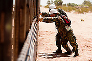 12 JUNE 2006 - SAN LUIS, AZ: National Guardsmen hold up a fence in San Luis, AZ. Mexico is a few feet behind the soldiers on the right. Fifty five members of the 116th Engineer Company, Combat Support Engineers, of the Utah Army National Guard are in San Luis, AZ, to build a fence and improve roads east of the San Luis Port of Entry on the US/Mexico border. The unit is the first of an estimated 6,000 US military personnel, almost all of them Army National Guard, who will be dispatched to the US/Mexico border by President Bush to help control immigration on the border. The Guardsmen will primarily build roads and fence and staff surveillance centers. They will not be engaged in first line law enforcement work.  Photo by Jack Kurtz
