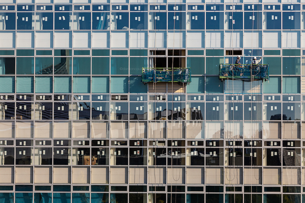 Workmen in gpndolas inspect the windows of a building that is being refurbished in Tokyo, Japan. Friday November 14th 2014