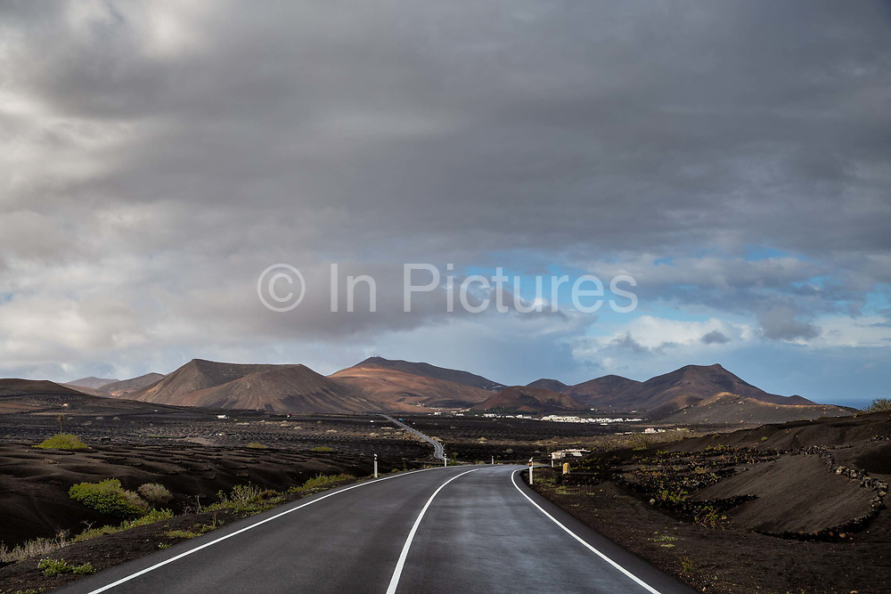 A road runs through an area where vines are cultivated in the traditional manner, protected by low curved stone walls on 26th November 2020, on the edge of Los Volcanes Natural Park in Lanzarote, Spain. The island was transformed by huge volcanic eruptions from 1731-36, which destroyed villages and much of the fertile wheat-growing land, and created the area now known as Timanfaya Natural Park. Farmers discovered that the volcanic soil was fertile and started cultivating the Malvasia Volcanica grape, and making Lanzarotes unique wines. .