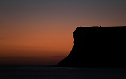 © Licensed to London News Pictures. <br /> 09/03/2015. <br /> <br /> Saltburn, United Kingdom<br /> <br /> The orange glow of dawn lights up the horizon at first light behind Huntcliff at Saltburn by the Sea.<br /> <br /> Photo credit : Ian Forsyth/LNP