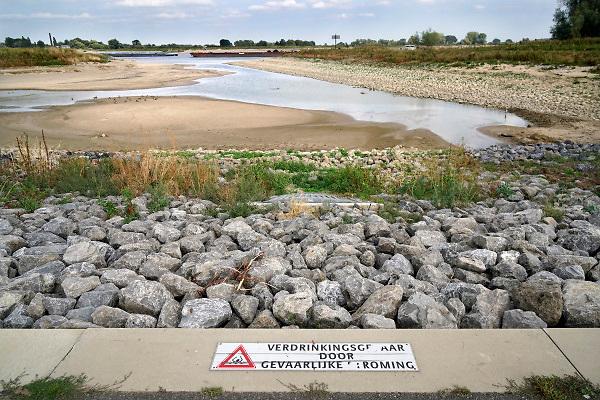 Nederland, Nijmegen, 19-8-2018Door de lage waterstand in de Waal is de aanvoer van water voor de Nevengeul, spiegelwaal, drooggevallen. De inlaten in de drempel liggen ver boven het water .Hierdoor stroomt de spiegelwaal niet meer door en is er blauwalg ontstaan zodat het een risico is erin te zwemmen . Bij de inlaten is altijd een zwemverbod van kracht . Foto: Flip Franssen