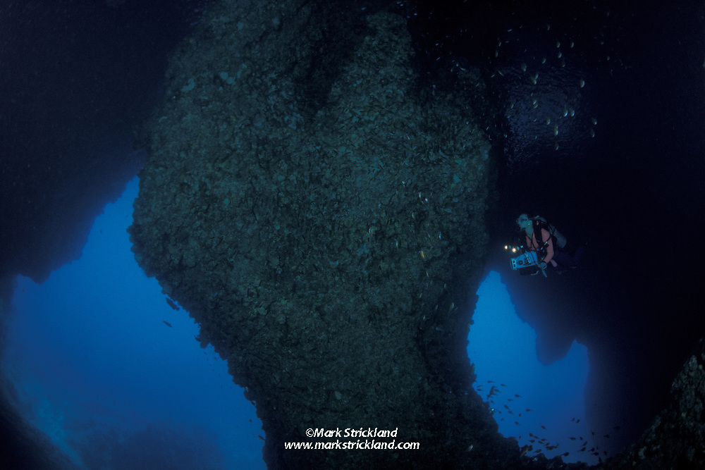 A diver explores a huge double cavern in one of Southern Thailand's many limestone karst formations.  Ko Ha Yai, Thailand, Andaman Sea