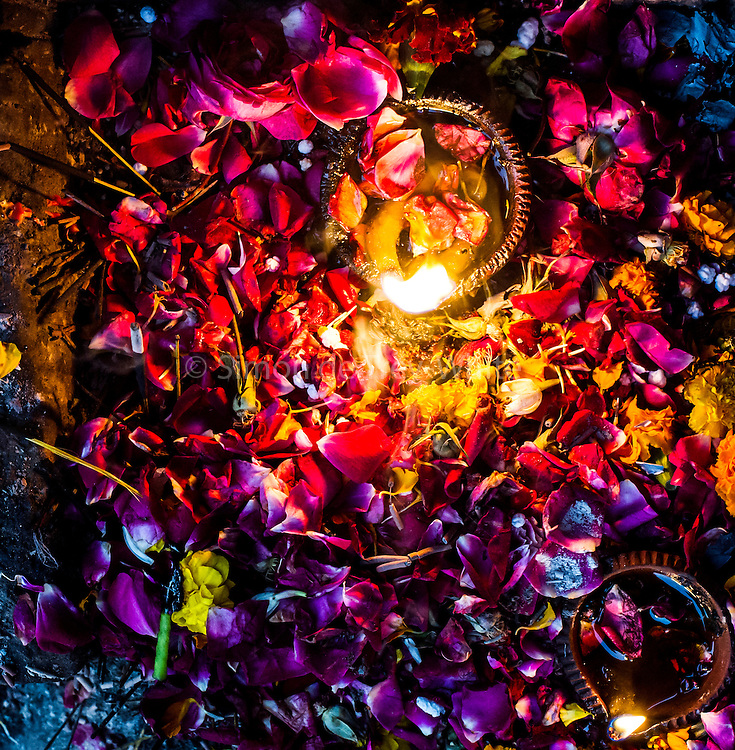 """15th January 2015, New Delhi, India. Flowers, petals, sweets and oil lamps left as offerings for wishes to be granted by Djinns in the ruins of Feroz Shah Kotla in New Delhi, India on the 15th January 2015<br /> <br /> PHOTOGRAPH BY AND COPYRIGHT OF SIMON DE TREY-WHITE a photographer in delhi. + 91 98103 99809. Email:simon@simondetreywhite.com<br /> <br /> People have been coming to Firoz Shah Kotla to leave written notes and offerings for Djinns in the hopes of getting wishes granted since the late 1970's. Jinn, jann or djinn are supernatural creatures in Islamic mythology as well as pre-Islamic Arabian mythology. They are mentioned frequently in the Quran  and other Islamic texts and inhabit an unseen world called Djinnestan. In Islamic theology jinn are said to be creatures with free will, made from smokeless fire by Allah as humans were made of clay, among other things. According to the Quran, jinn have free will, and Iblīs abused this freedom in front of Allah by refusing to bow to Adam when Allah ordered angels and jinn to do so. For disobeying Allah, Iblīs was expelled from Paradise and called """"Shayṭān"""" (Satan).They are usually invisible to humans, but humans do appear clearly to jinn, as they can possess them. Like humans, jinn will also be judged on the Day of Judgment and will be sent to Paradise or Hell according to their deeds. Feroz Shah Tughlaq (r. 1351–88), the Sultan of Delhi, established the fortified city of Ferozabad in 1354, as the new capital of the Delhi Sultanate, and included in it the site of the present Feroz Shah Kotla. Kotla literally means fortress or citadel."""