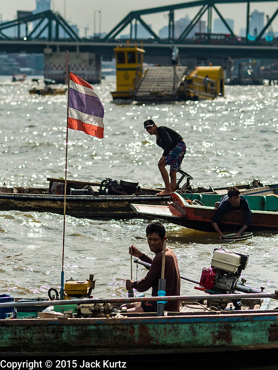 14 OCTOBER 2015 - BANGKOK, THAILAND:  Spotters on dive boats wait for the divers they work with, who are on the bottom of the Chao Phraya River in Bangkok. Divers work in two man teams on small boats in the Chao Phraya River. One person stays in the boat while the diver scours the river bottom for anything that can be salvaged and resold. The divers usually work close to shore because the center of the river is a busy commercial waterway with passenger boats and commercial freight barges passing up and down the river all day long. The Chao Phraya is a dangerous river to dive in. It's deep, has large tidal fluctuations, is fast flowing and badly polluted. The divers make money only when they sell something.   PHOTO BY JACK KURTZ
