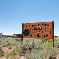 """Along Indian Rte 9301, a sign reads, """"When you Refuse to Reuse, it's our Earth you Abuse!!"""" in St Michaels, AZ."""