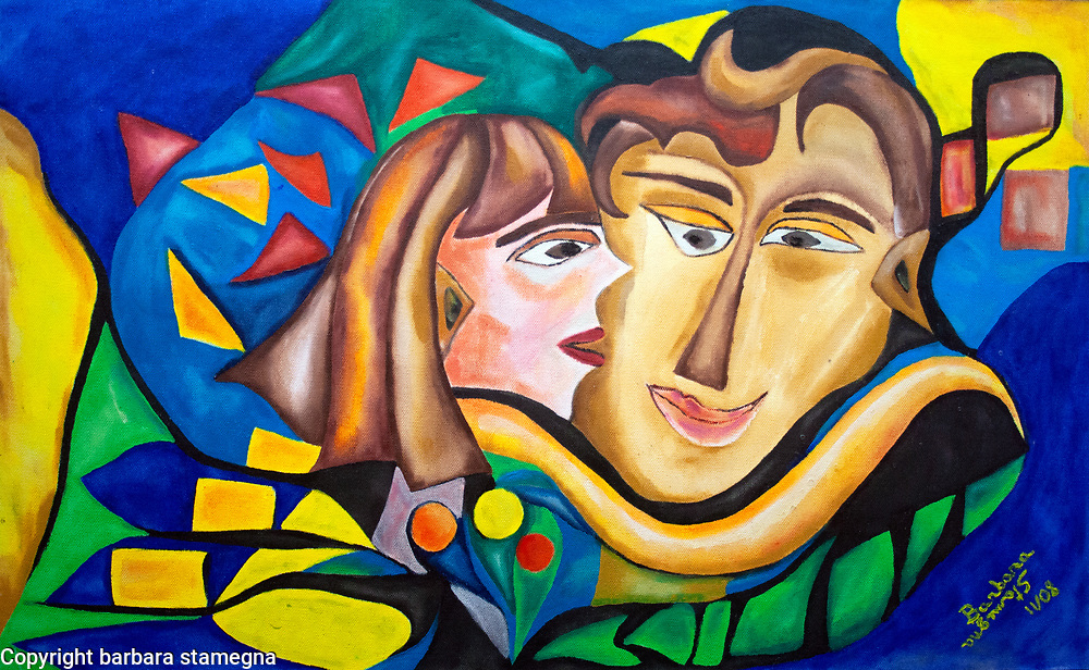 abstract image in red, orange, yellow, black, white, blue, green and pink tones with a  woman and man heads central figure and the woman in the act  kissing the man's cheek, with abstract round and bended shapes and geometric forms.
