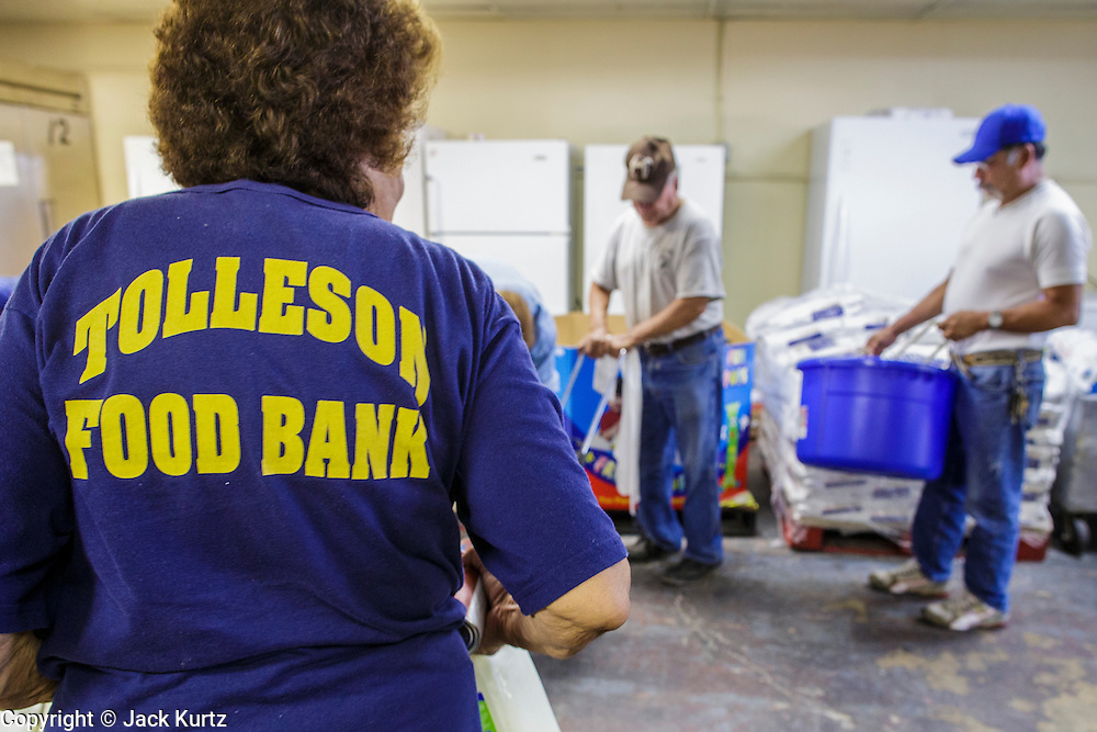 07 AUGUST 2012 - TOLLESON, AZ: A volunteer loads a clients basket at the food bank in Tolleson, AZ, about 15 miles west of Phoenix. The Tolleson food bank has been operating for more than 20 years. It used to serve mostly the families of migrant farm workers that worked the fields around Tolleson but in the early 2000's many of the farms were sold to real estate developers. Now the food bank serves both farm worker families and people who lost their homes in the real estate crash, that his Phoenix suburbs especially hard. More than 150 families a day are helped by the Tolleson food bank, an increase of more than 50% in the last five years.   PHOTO BY JACK KURTZ