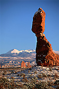 A rare winter snow covers Balanced Rock in the desert of Utah's Arches National Park and the Unita Mountains in the distance.