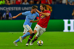 Manchester United midfielder Daley Blind (17) wins the ball from Manchester City midfielder Patrick Roberts (27) during the International Champions Cup match between Manchester United and Manchester City at NRG Stadium in Houston, Texas
