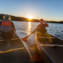 A woman paddles a canoe at dawn on Silver Lake in Piscataquis County, Maine. Near Greenville.