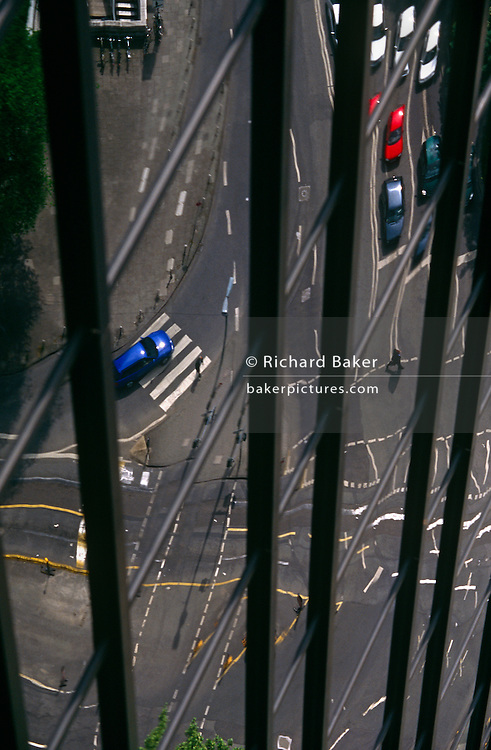 Reflected and distorted landscape of a road junction and pedestrians seen through Frankfurst office building windows.