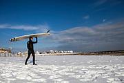 Mark Kielpinski, of Brewster, MA, walks across a snowy beach to go surfing at Green Harbor in Marshfield, MA, on a cold February day.